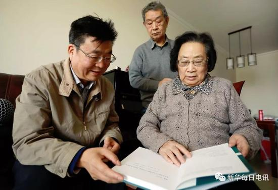 屠呦呦(右)向本报记者介绍青蒿素相关文献。新华社记者 孟菁摄