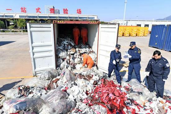 2017年12月21日,厦门海关工作人员在海沧查验场查验走私的进口牛皮革洋垃圾。(新华社)