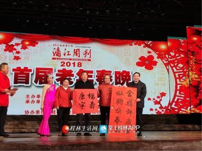 在歌声中,旗风雅韵、八桂斋书法、瓷画也一并在台上呈现给观众。图为市领导接受书法家的对联赠礼。