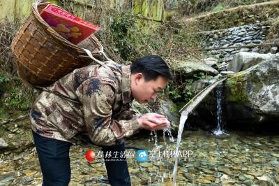在大山里行走,冰冷的溪水也浇灭不了他扶贫的热情。