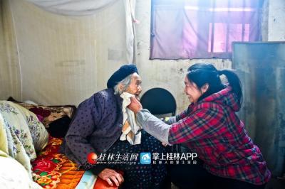 陈绪英在帮助村里一位贫困户的母亲擦脸。