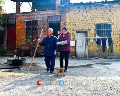 陈绪英搀扶一位有视力问题的贫困户出门晒太阳。
