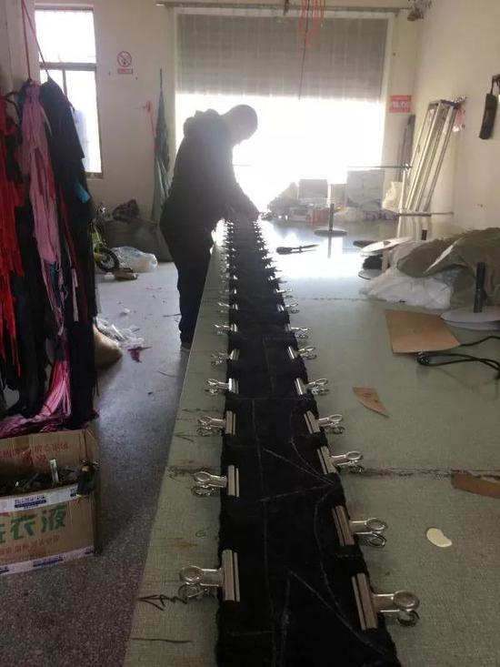 高秋霞和老公在布料上画版剪裁。新京报记者陶若谷 摄