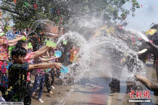 资料图:泰国大象用鼻子向参加泼水节庆典的人群喷水。