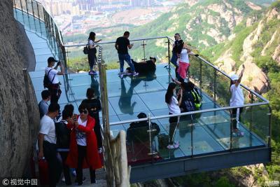 """2018年5月9日,辽宁丹东凤凰山景区现数百米高空玻璃栈道,该玻璃栈道长度42米、垂直高300度,观景台面积30平方米。绝壁凌空惊险刺激的玻璃栈道""""吓坏""""了不少前来参观的游客。"""
