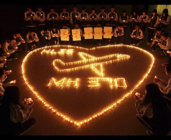 资料图片:中国学生点燃蜡烛为MH370乘客祈福。