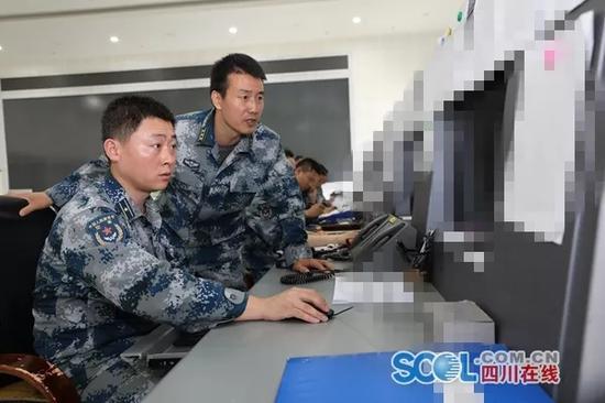 航空管制值班员辛鑫(左)和战友在操作台察看当天空中航线情况 本文图均为 四川在线 图