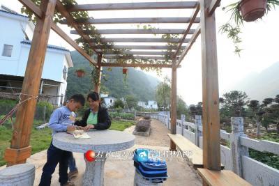 平乐县沙子镇渡河村不断完善基础设施建设,农村人居环境越来越优美。图为村民在村中回廊下辅导孩子做功课。记者何平江 摄