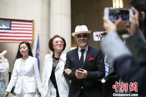 资料图:当地时间5月24日,周立波与妻子胡洁走出法庭。中新社记者 廖攀 摄