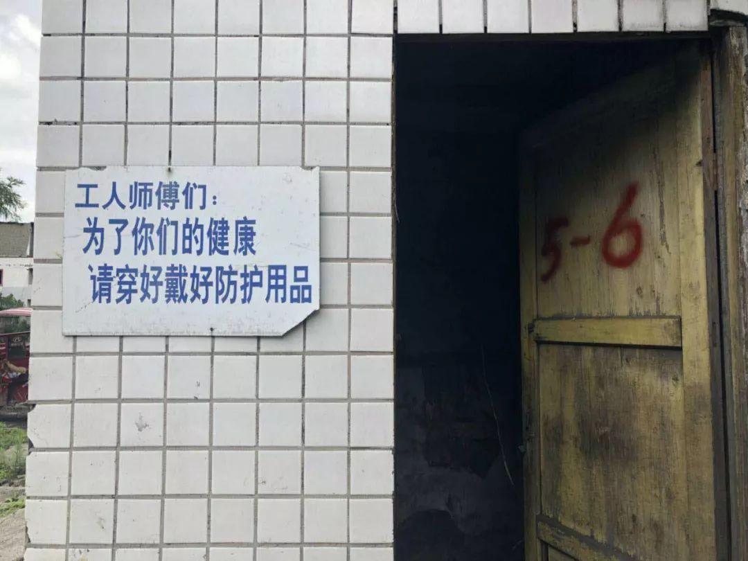 矿区墙上写着提醒工人戴好防护用品的标语。新京报记者 王翀鹏程 摄