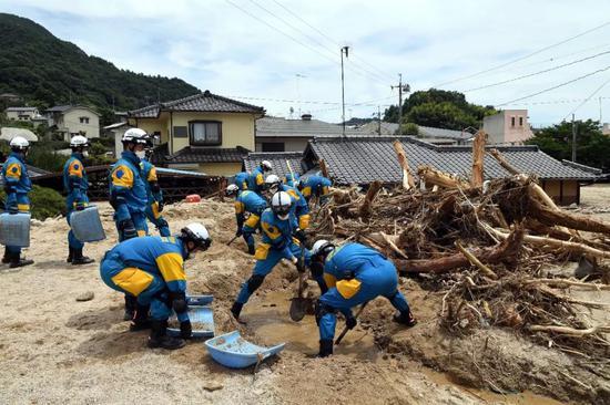 7月11日,在日本广岛吴市天应町地区,警察清理民居附近的泥沙。新华社记者马平摄