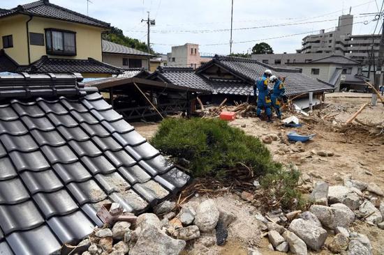 7月11日,在日本广岛吴市天应町地区,警察挖掘被泥石流淹没的民居。新华社记者马平摄