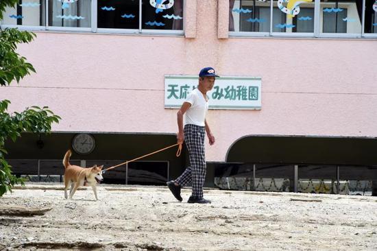 7月11日,在日本广岛吴市天应町地区,一名居民走过被泥石流部分淹没的幼儿园。新华社记者马平摄