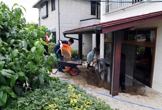 7月11日,在日本广岛吴市天应町地区,居民清理房屋外的泥沙。新华社记者马平摄