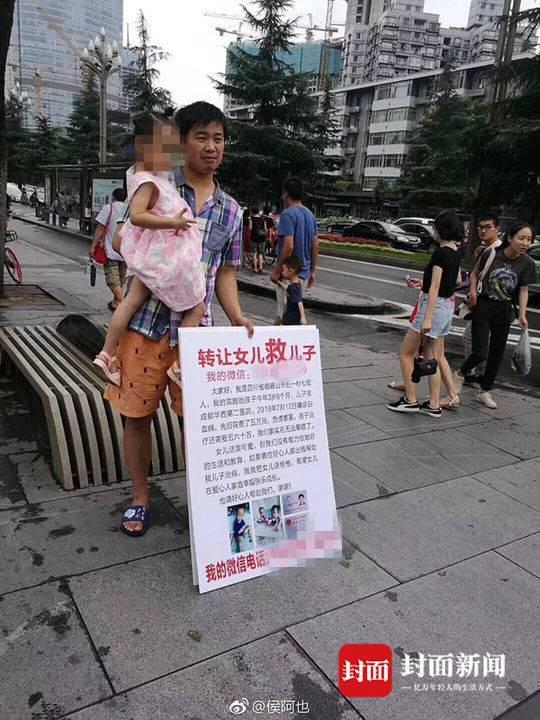 """梁育佳站在街头,怀里抱着女儿,面前放着一块牌子:""""转让女儿救儿子。"""""""