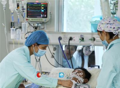 在ICU病房里,韦妍飞为病人进行检查,一旁的窗外,家属们进行床旁探视。
