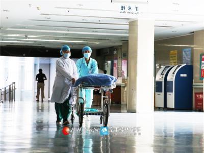 韦妍飞和同事推着推车接从手术室出来的重病患者。