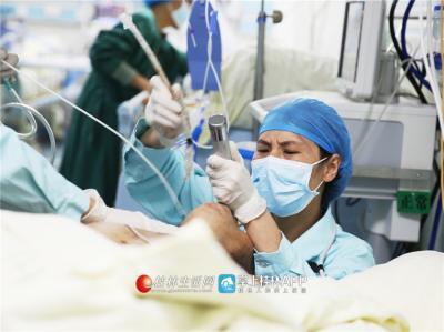 韦妍飞半蹲着为病人进行气管插管。