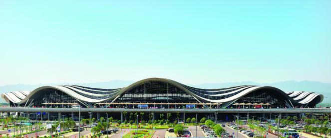 """""""国际范""""的桂林两江国际机场T2航站楼,造型设计以桂林山水甲天下为灵感,山水般起伏流动的屋面线条和天际线构成一顶靓丽的""""山水桂冠"""",使机场与山水融为一体。"""