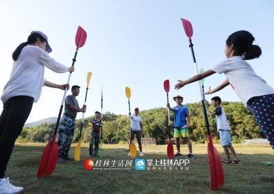 开始运动前,大家一起在花江农场的草?#33655;?#20570;热身活动。