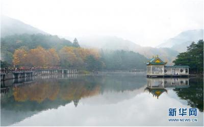 这是10月20日拍摄的如琴湖。当日,位于江西省九江市庐山风景区内的如琴湖云雾缭绕,层林尽染,吸引众多游客前来观赏游玩。新华社记者 胡晨欢 摄