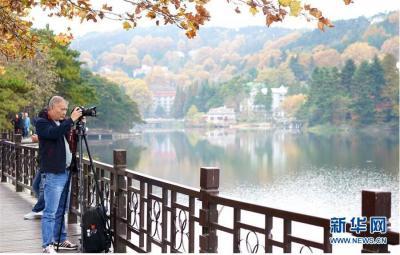 游客在九江市庐山风景区内的如琴湖旁摄影(10月20日摄)。当日,位于江西省九江市庐山风景区内的如琴湖云雾缭绕,层林尽染,吸引众多游客前来观赏游玩。新华社记者 胡晨欢 摄
