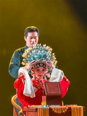 一位白衣女孩在台上描眉点唇,两位检场人手捧凤冠霞帔侍候一旁,后台被搬到了前台,寻常的扮戏过程在此间便有了神圣庄严的仪式感。