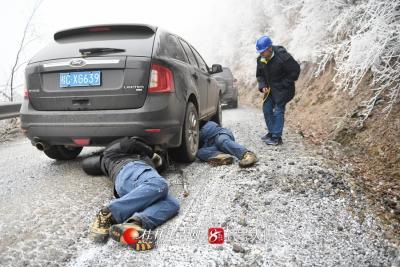 《装防滑链》12月30日,新一轮强冷空气来袭,广西桂林资源县气温降至冰点,广西电网桂林供电局输电人员顶着严寒,到60公里外的山上巡视覆冰的电网覆冰线路,低温导致道路结冰,图为工作人员正钻到车底为车辆安装防滑链,以便安全到达观冰点。 莫希涛 摄