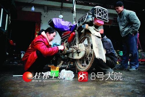 陈兰与老公一起修理一辆摩托车。
