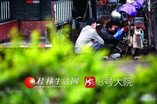 陈兰的老公石全茂(右)在给一村民修摩托车。