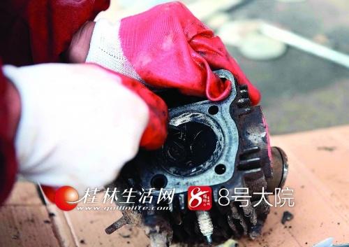 陈兰在修理一辆摩托车的发动机。