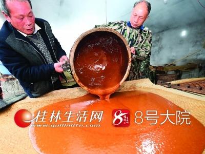 在榨糖作坊里,廖瑞林和榨糖师傅一起把熬制好的糖水倒在竹席上晾凉。