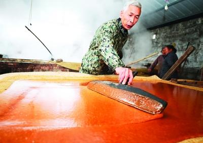 榨糖师傅黄胜芳熟练地把熬制好的红糖抹平成型。