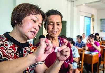 在县老年大学里,黄惠玲指导学生剪纸。