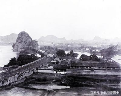 """清末桂林房舍与城墙。城墙右边的湖为以前的八角塘,位于独秀峰北面,叠彩山南面,是一个由于地理原因下雨积水形成的池塘。宋朝时,广西经略安抚使程节于宋昭圣四年(1097年)在现在的八角塘南面兴建了""""八桂堂"""",是桂林最早的人工园林。"""
