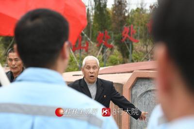 3月25日,在湘江战役光华铺阻击战烈士墓前,兴安县界首镇城东村委老屋场82岁的老党员刘发亮激动地向前来缅怀悼念的供电所党员讲述当年红军浴血奋战的故事。莫晓姣摄