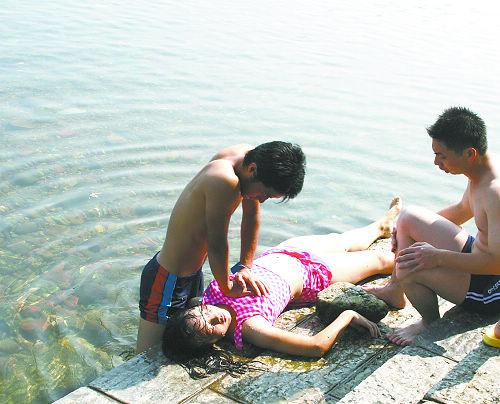溺水女孩的朋友正给她实施急救
