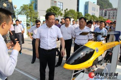 图为市委书记、市人大常委会主任刘君在详细了解曾在汶川地震中为救灾提供了大量宝贵的图片资料的桂林无人机。