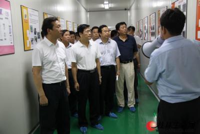 在桂林尚科光伏技术有限责任公司太阳能电池片生产车间,公司总经理许添居汇报产品生产情况。