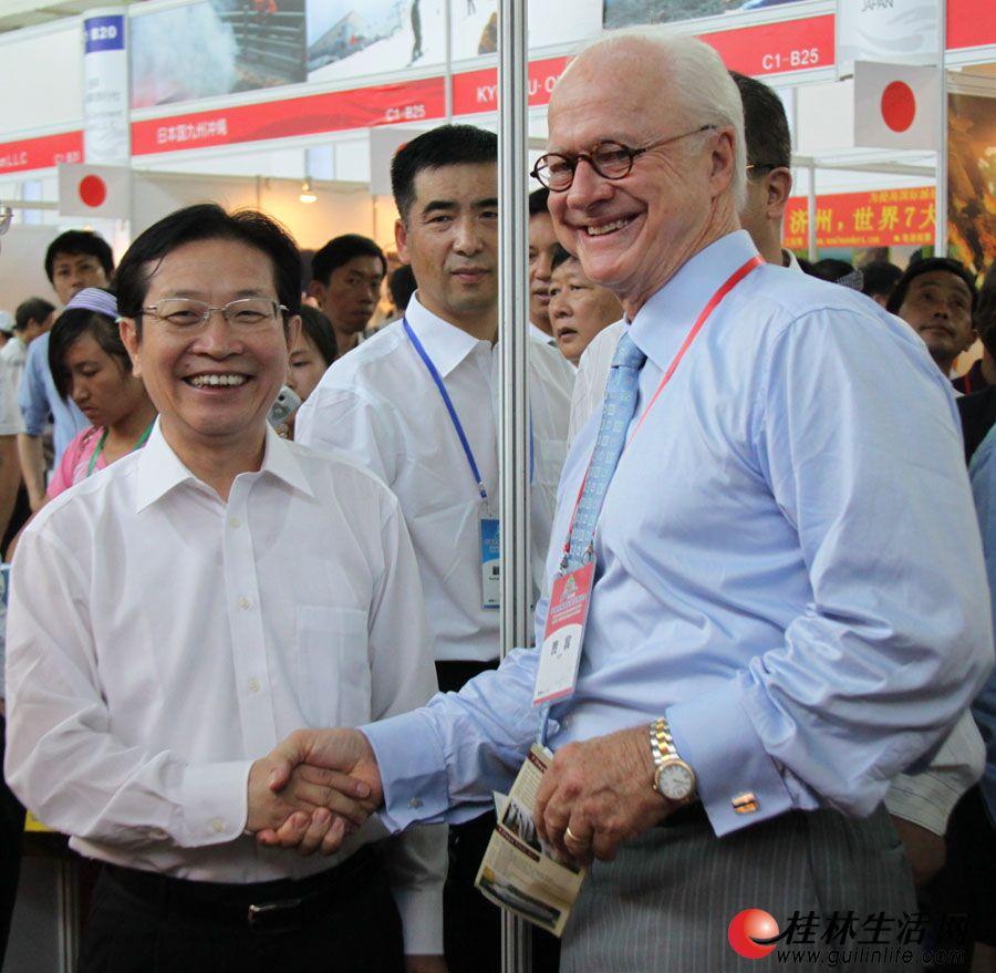 广西壮族自治区人民政府副主席高雄(左)巡视展馆,并与外国友人亲切交流。