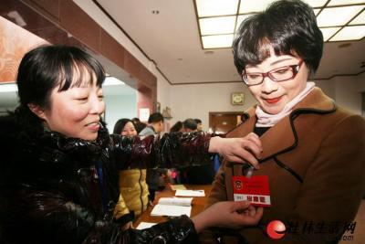 1月29日,工作人员帮与会人员佩戴出席证。 记者李凯 摄