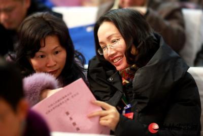 1月29日下午,两位与会人员在认真阅读刚拿到的大会服务指南。   记者刘教清 摄