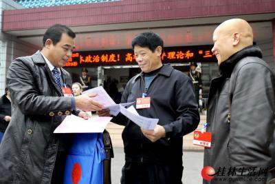 1月29日下午,出席政协桂林市四届二次会议的委员们在市直机关小礼堂报到后,查看会议材料  记者何平江 摄