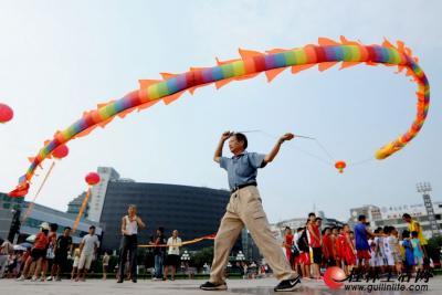 """8月8日,一名空竹爱好者在桂林市中心广场抖""""空竹龙""""。(何平江 摄)"""