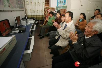 """11月8日上午,解西社区内老党员与社区干部一起收看""""十八大""""开幕。 记者李凯 摄"""