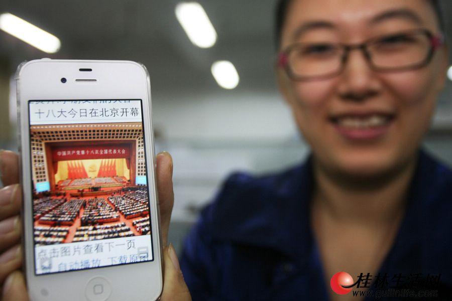 """11月8日上午,桂林理工大学的潘老师在上课的间隙,不忘拿出手机查看""""十八大""""的实况报道。 记者李凯 摄"""