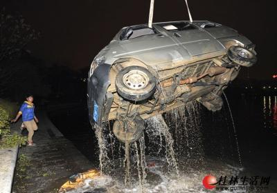 柳微车被吊车从湖里吊起。  记者李凯 摄