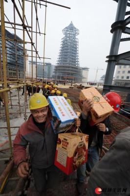 """临桂""""一院两馆""""建设工地上,农民工们扛着刚领到的节日礼物,开心的表情洋溢在脸上。记者唐艳兰 摄"""