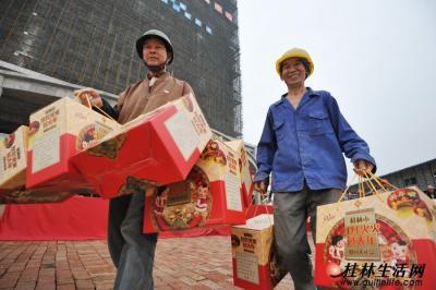 """去年底已经封顶的桂林日报社传媒中心大楼前,两名大楼建设者提着刚领到的""""春节大礼包""""开心地走过。记者何平江 摄"""