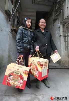 """丽君社区的生活困难母女领到志愿者送来的""""春节大礼包""""后露出了笑容。记者刘教清 摄"""